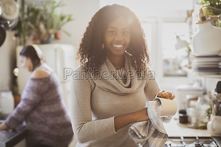 portrait happy young woman drying dishes