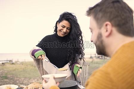 happy woman serving chowder to boyfriend