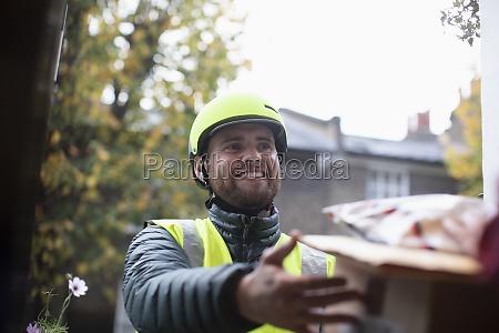 happy friendly male courier in helmet
