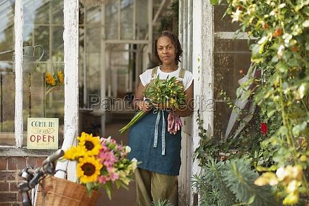 portrait confident female florist with bouquet