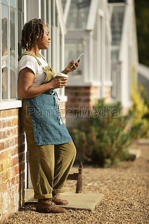 female garden center owner enjoying coffee