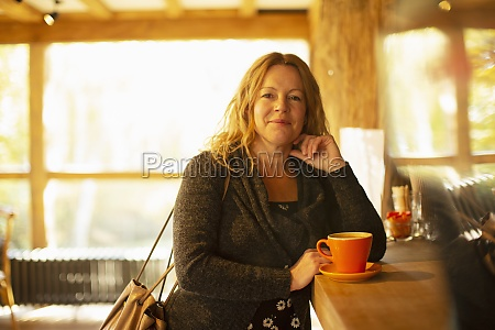portrait happy woman ordering cappuccino at