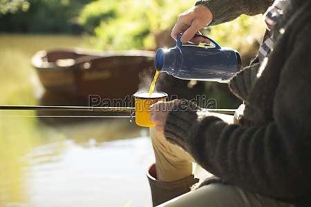 man fly fishing and pouring coffee