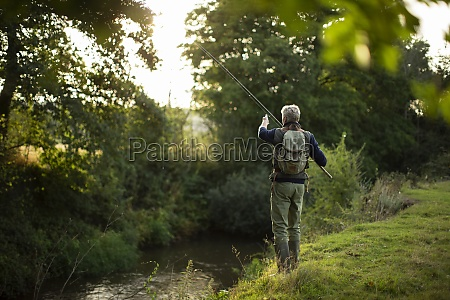 man in backpack fly fishing at
