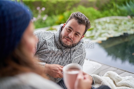 man listening to wife on patio