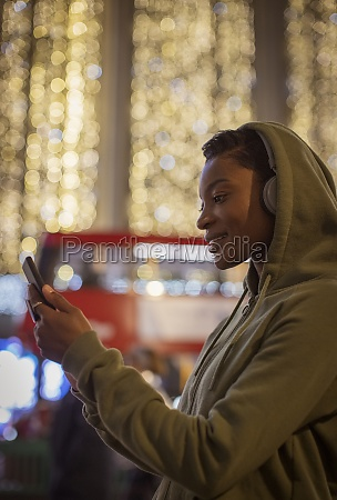 young woman in hoody using smart