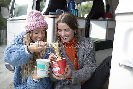young women friends sharing instant noodles