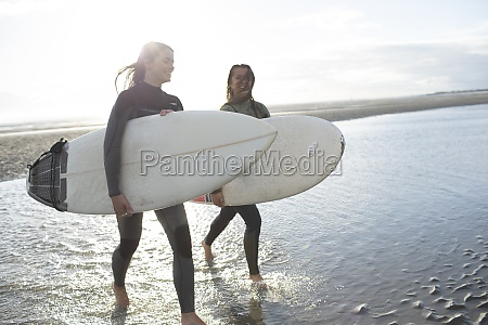 young female surfers wading in sunny
