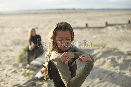 young female surfer putting on wet