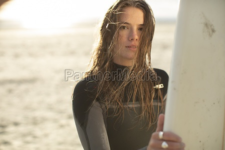 portrait beautiful young female surfer in
