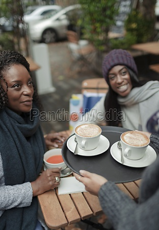 waitress serving cappuccinos to mother and
