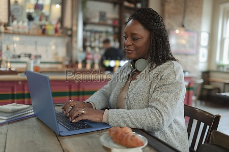 woman working at laptop in cafe