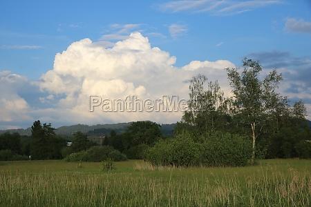 dramatic cumulus cloud over green meadows