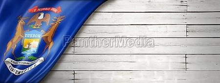 michigan flag on white wood wall