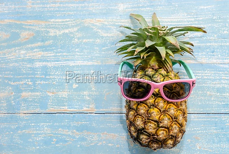 pineapple with pink sunglasses on blue