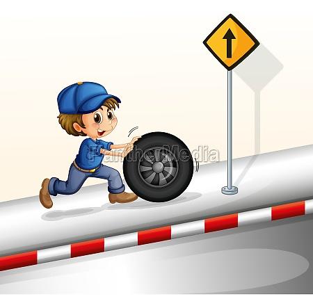 a smiling mechanic pushing the tire