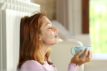 woman relaxing on radiator holding coffee