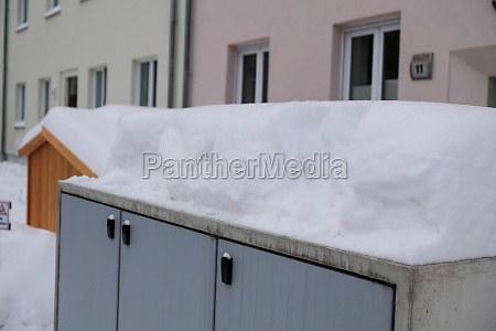 an extremely snowy electricity box in