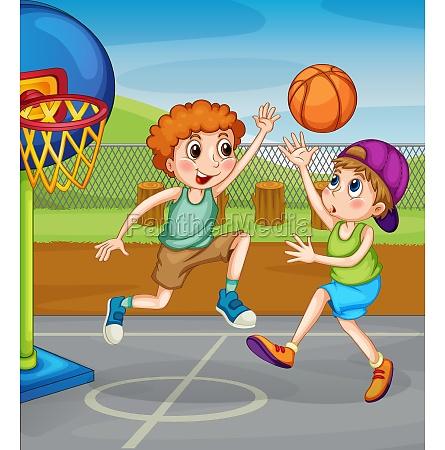 two boys playing basketball outside