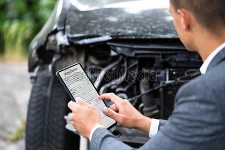 insurance agent inspecting damaged car