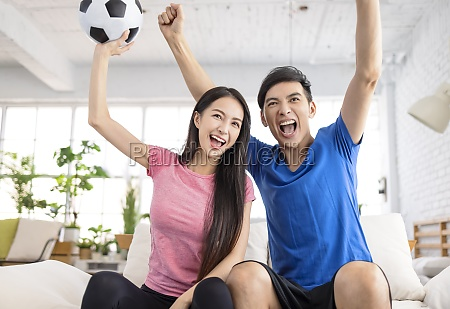 excited young couple watching tv and