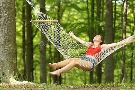 excited woman swinging on hammock celebrating