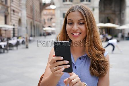 cool fashion girl using smartphone in