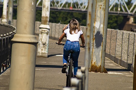 girl rides a bicycle back view