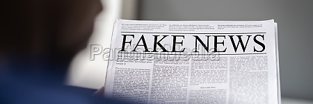 african man reading fake news headline