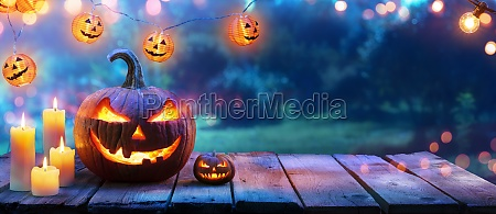 pumpkin with candles on table in