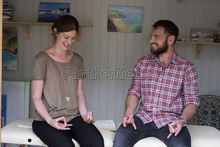 man and therapist seated with hands