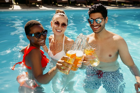 friends drink beverages in the pool