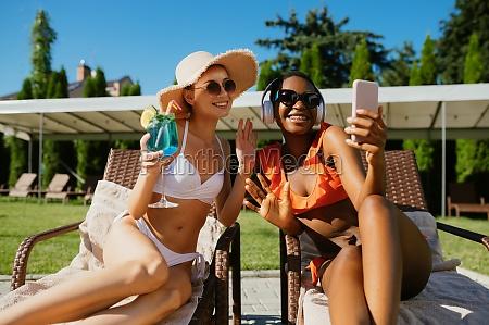 two girlfriends make selfie on sun