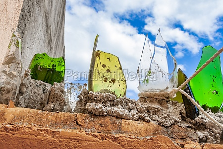 wall with broken glass bottles in