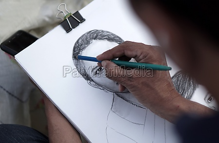 indian artist drawing pencil portrait of