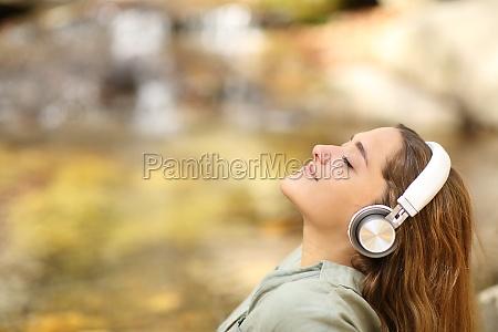 woman breathing fresh air listening to