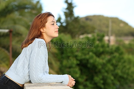 woman contemplating views from balcony of